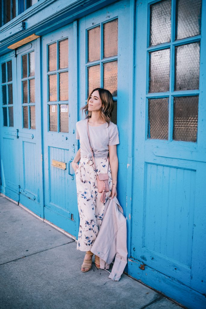 Blogger Mary Krosnjar wearing Floral Jumpsuit with grey tee and grey moto jacket