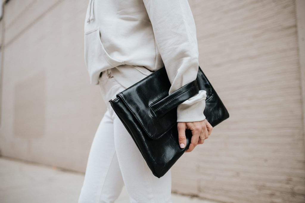 Blogger Mary Krosnjar wearing folded black clutch