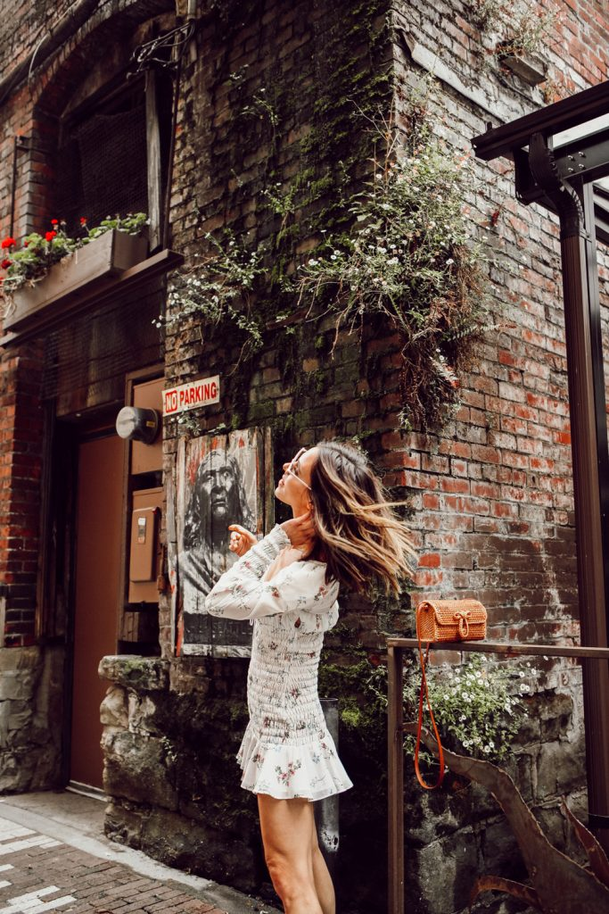 Seattle Fashion Blogger Sportsanista wearing white floral smocked dress in Pioneer Square, Seattle