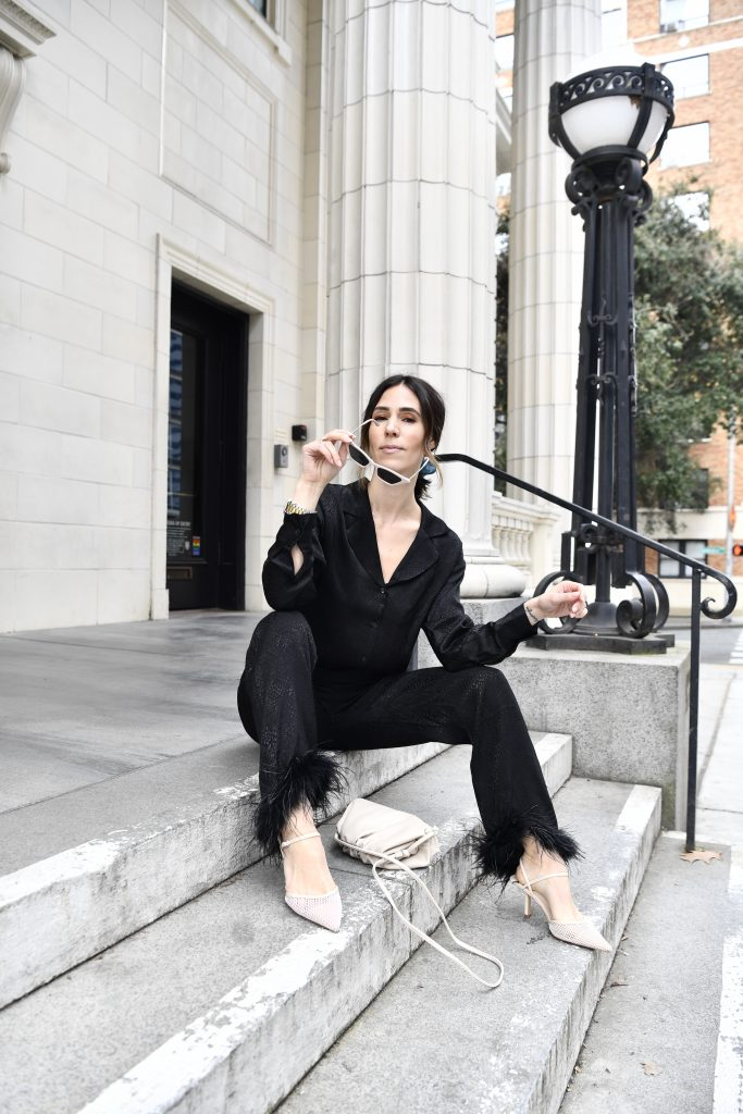 Blogger Sportsanista wearing black silk blouse, black silk pants with ostrich feather trim and mesh nude pumps