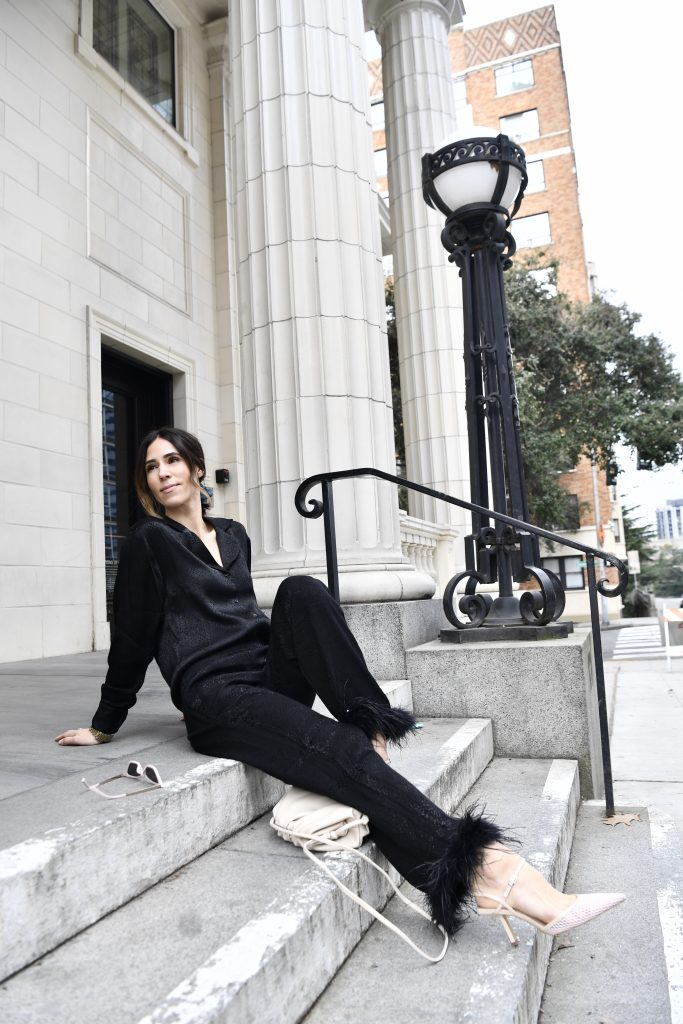 Blogger Mary Krosnjar wearing black silk blouse and black silk pants with ostrich feather trim