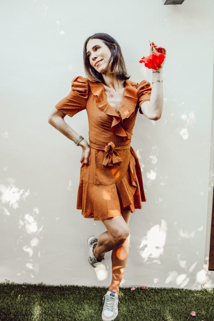 Blogger Sportsanista sharing ruffle wrap mini dress and golden goose sneakers